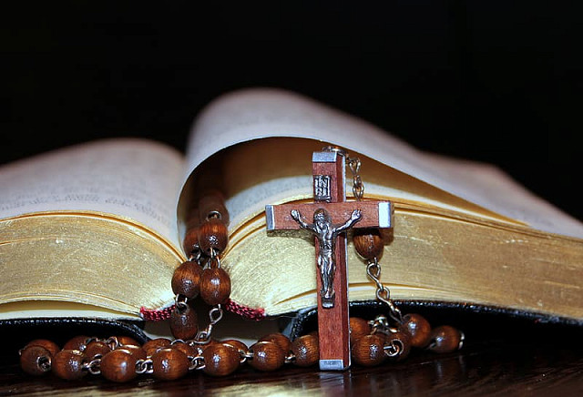 Brown rosary and open bible
